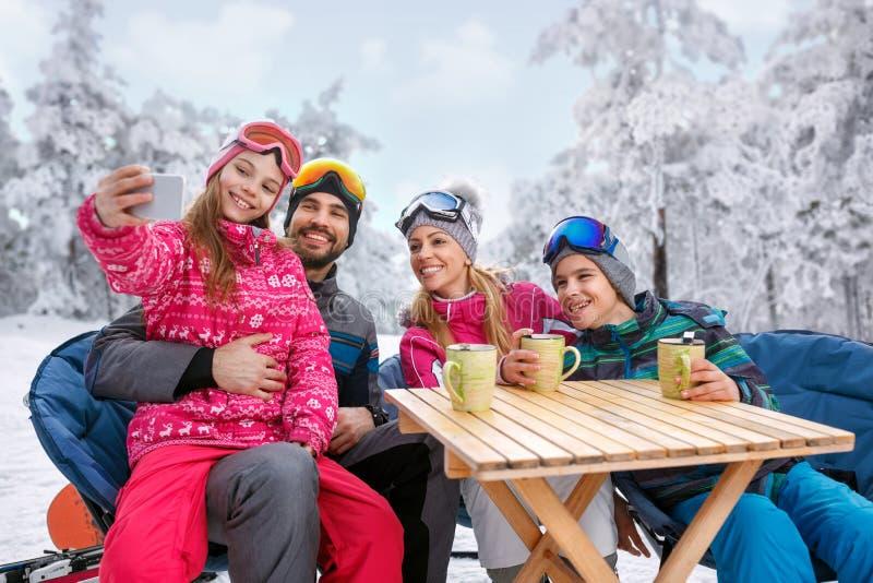 Chica joven con la familia que goza en vacaciones del invierno en nieve y m imagen de archivo