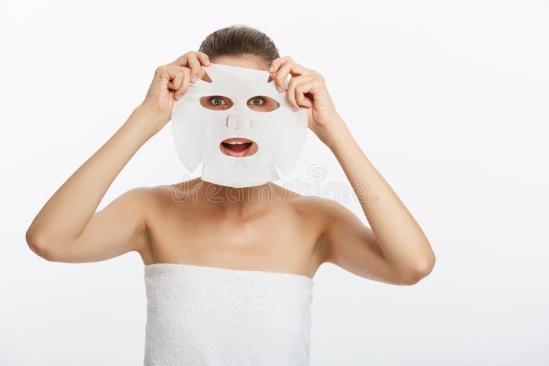 Chica joven con la máscara facial que mira la cámara sobre el fondo blanco Procedimiento cosmético Balneario y cosmetología de la imagen de archivo libre de regalías
