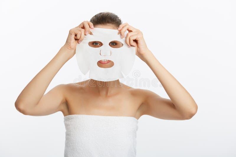Chica joven con la máscara facial que mira la cámara sobre el fondo blanco Procedimiento cosmético Balneario y cosmetología de la fotos de archivo libres de regalías