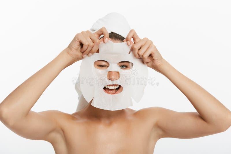 Chica joven con la máscara facial que mira la cámara sobre el fondo blanco Procedimiento cosmético Balneario y cosmetología de la foto de archivo