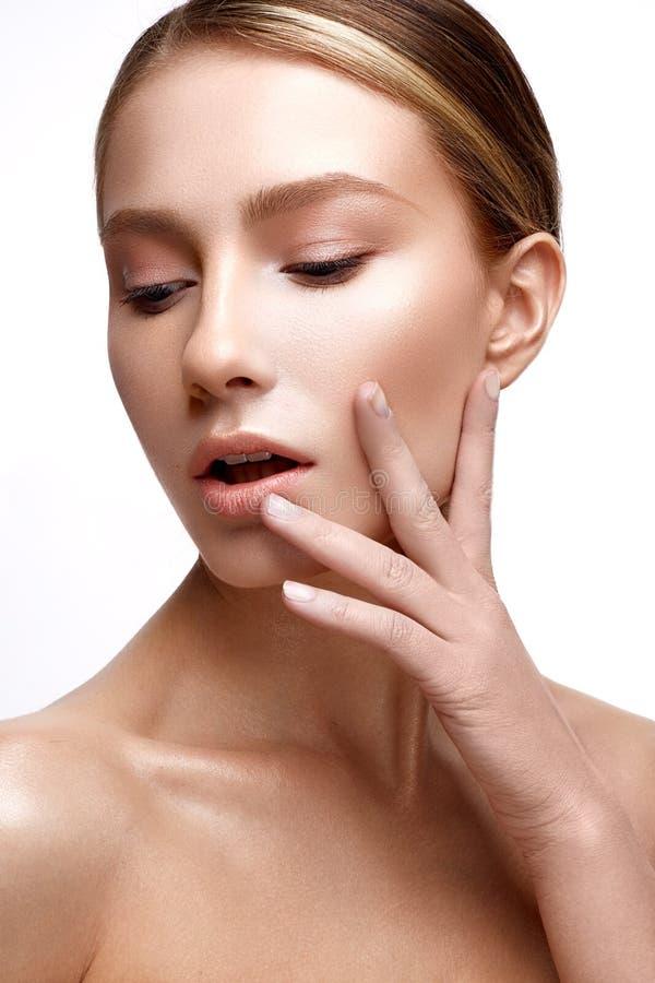 Chica joven con la piel brillante perfecta Un modelo hermoso con un maquillaje de la fundación y del desnudo Limpie la piel Fondo foto de archivo libre de regalías