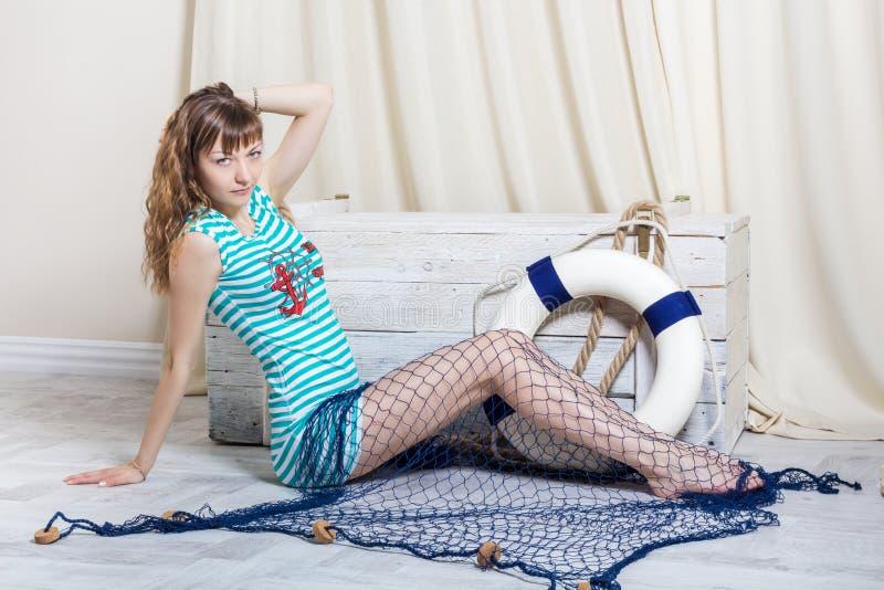 Chica joven con la red del mar que se sienta en piso fotografía de archivo
