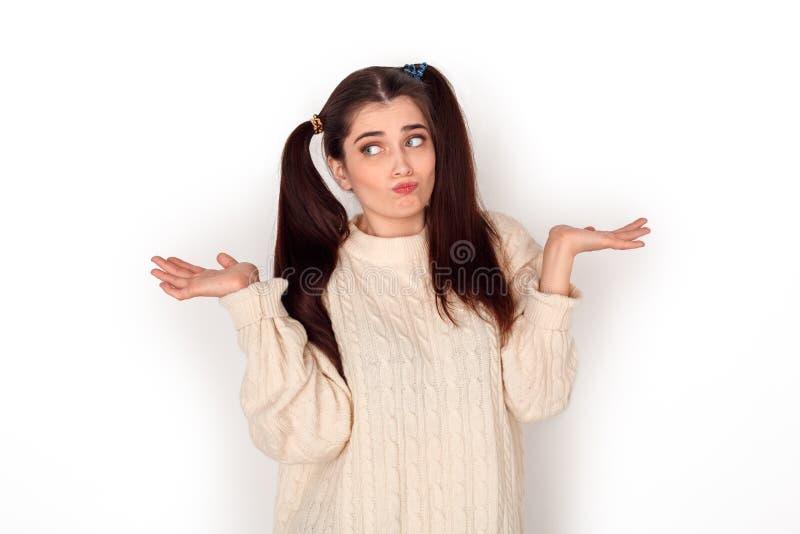 Chica joven con la situación del estudio de dos colas de caballo aislada en las manos blancas a un lado confundidas foto de archivo libre de regalías