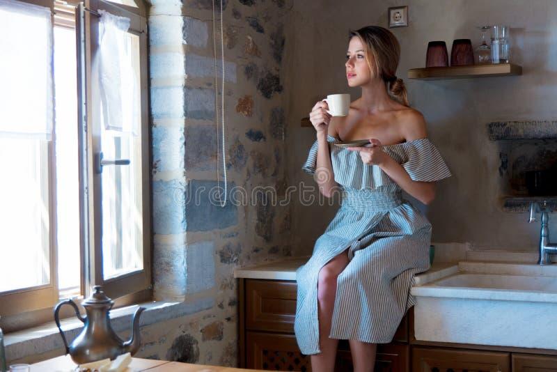 Chica joven con la taza de café o de té en la cocina griega fotos de archivo