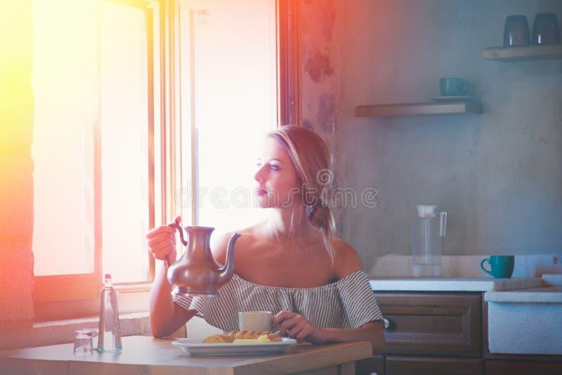 Chica joven con la taza de café o de té en la cocina griega fotografía de archivo libre de regalías