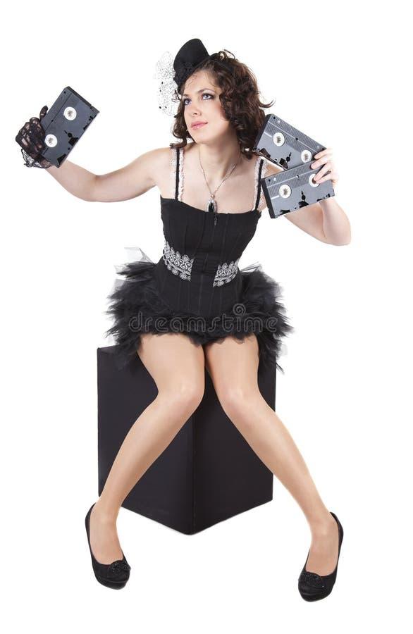Chica joven con las cintas de video viejas foto de archivo libre de regalías