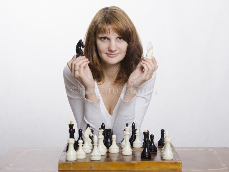 Chica joven con las figuras caballo, ajedrez fotos de archivo libres de regalías
