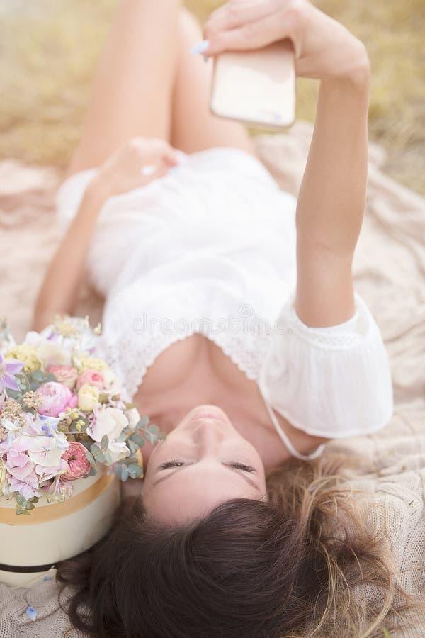 Chica joven con las flores en el sombrero del verano que presenta en campo foto de archivo