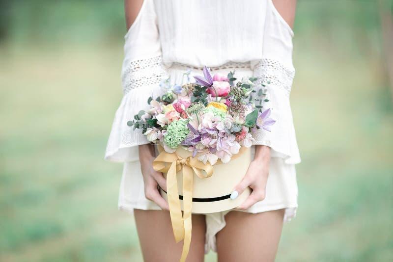 Chica joven con las flores en el sombrero del verano que presenta en campo fotos de archivo libres de regalías