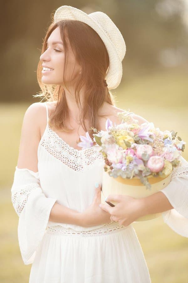 Chica joven con las flores en el sombrero del verano que presenta en campo imagenes de archivo