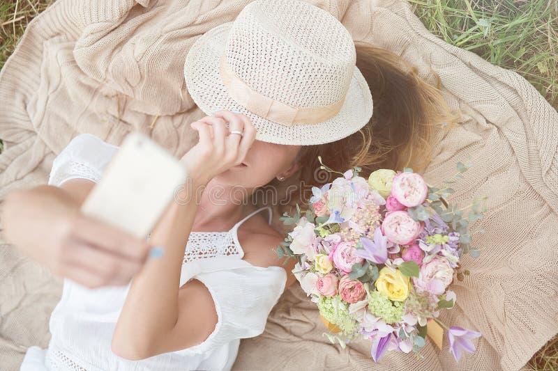 Chica joven con las flores que hacen el selfie en campo foto de archivo libre de regalías