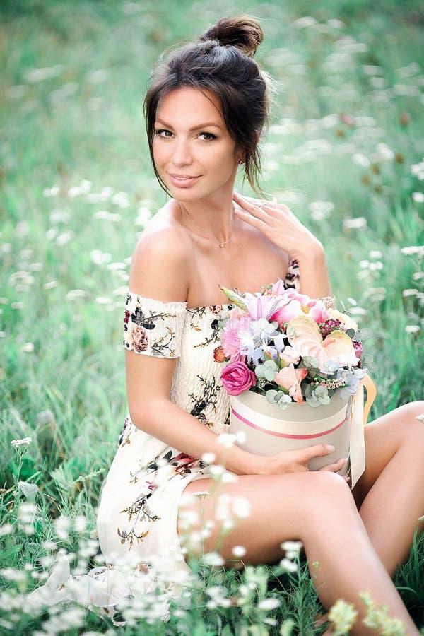 Chica joven con las flores que presentan en campo foto de archivo