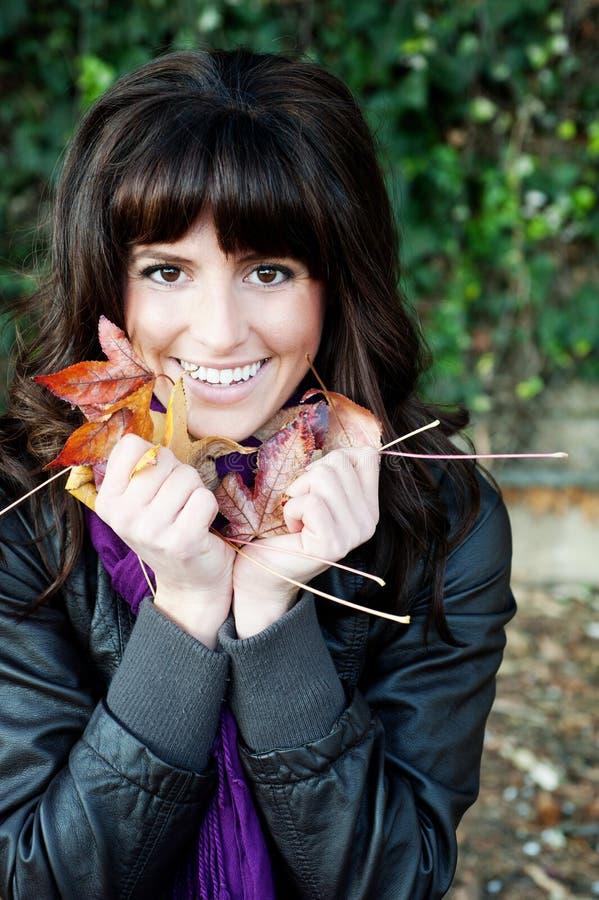 Chica joven con las hojas de otoño imagenes de archivo