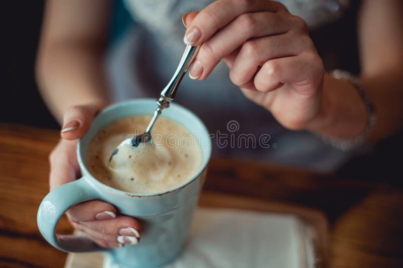 Chica joven con las manos agradables con la manicura francesa blanca que mezcla un coffe en taza azul del vintage imágenes de archivo libres de regalías