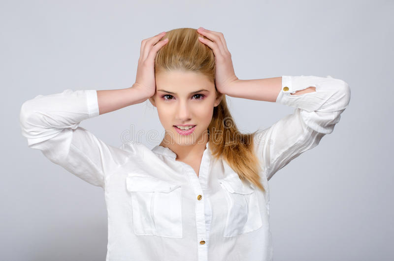 Chica joven con las manos en su cabeza que está desesperada. imagen de archivo