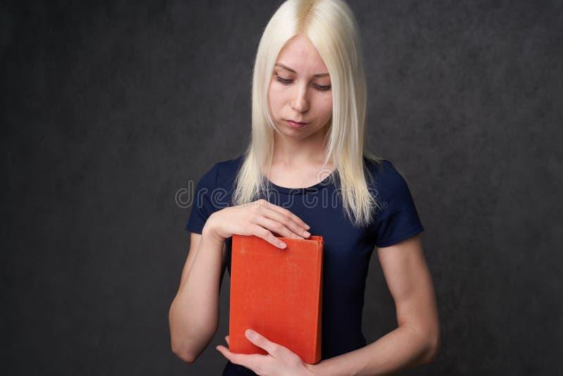 Chica joven con las pecas que sientan el retrato de un estudiante De nuevo a concepto de la escuela fotografía de archivo