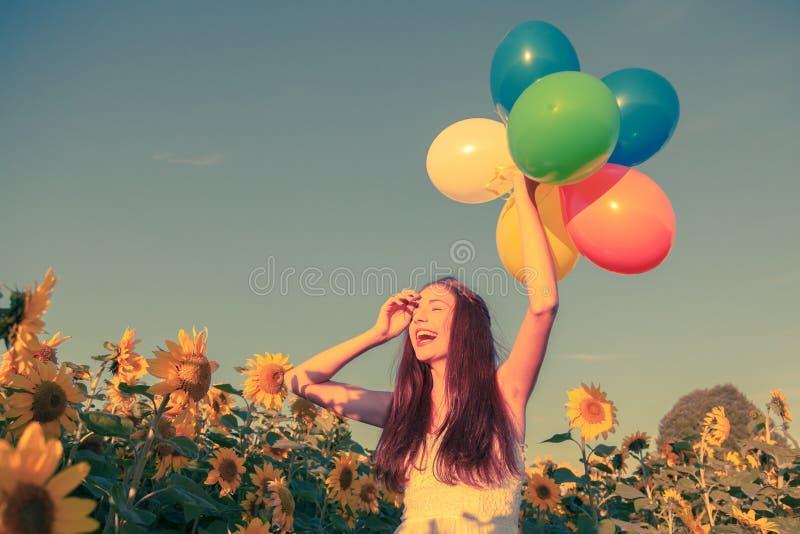 Chica joven con los globos en un campo del girasol imagen de archivo libre de regalías