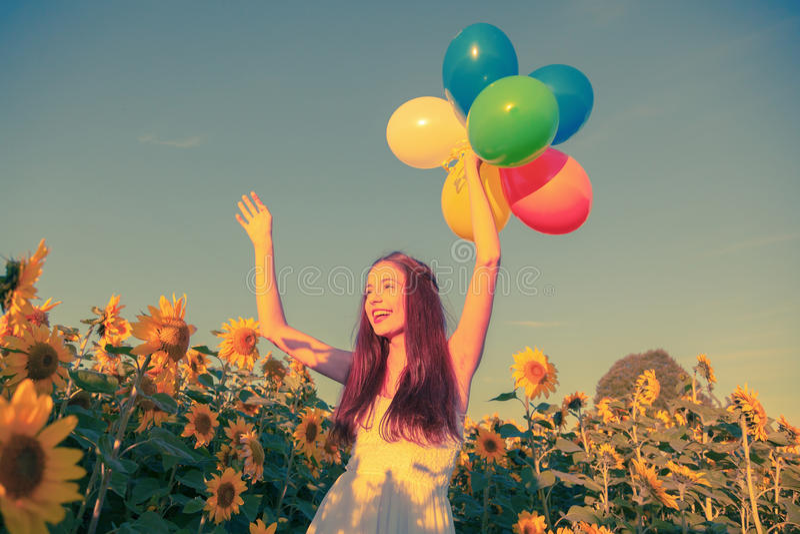 Chica joven con los globos en un campo del girasol imagenes de archivo