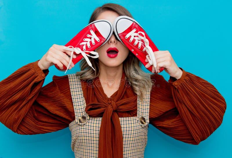 Chica joven con los gumshoes rojos fotos de archivo
