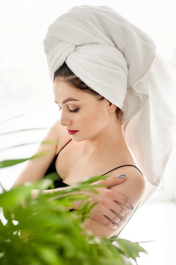 Chica joven con los ojos grandes y las cejas oscuras, toalla blanca que lleva en el maquillaje desnudo ligero principal, foto de  imagen de archivo