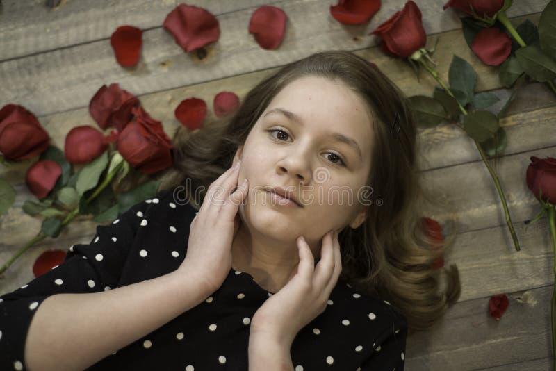 Chica joven con los pétalos color de rosa que ponen en el piso imágenes de archivo libres de regalías