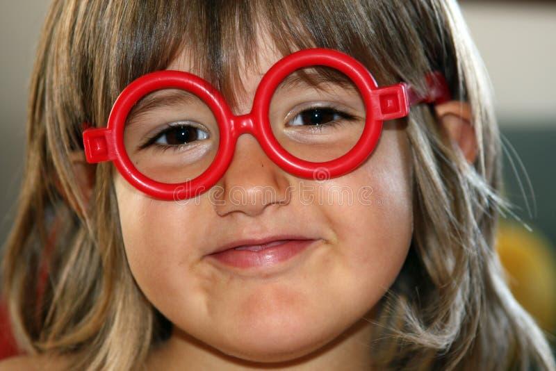 Chica joven con los vidrios rojos fotos de archivo libres de regalías