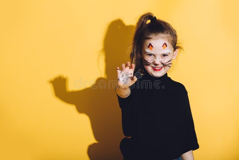Chica joven con maquillaje del gato en su cara foto de archivo