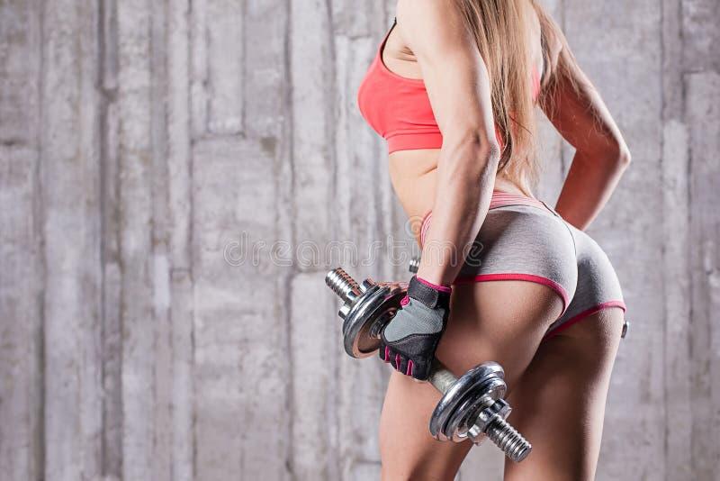 Chica joven con pesas de gimnasia y nalgas tensas imagen de archivo