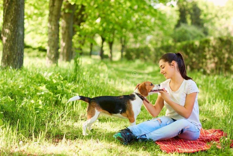 Chica joven con su perro en el parque Muchacha, perro, beagle fotos de archivo libres de regalías