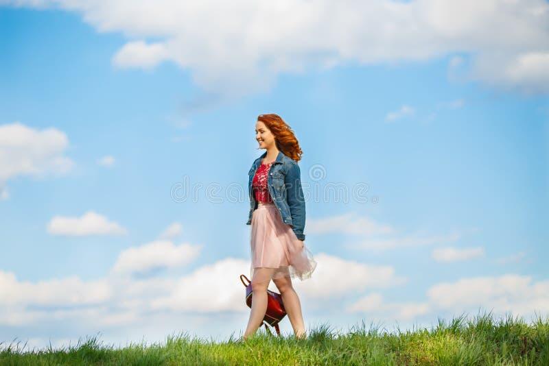 Chica joven con un bolso en fondo de la hierba verde y del cielo azul fotografía de archivo