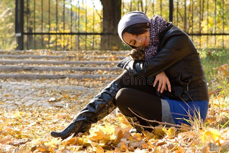 Chica joven con un gatito al aire libre fotos de archivo