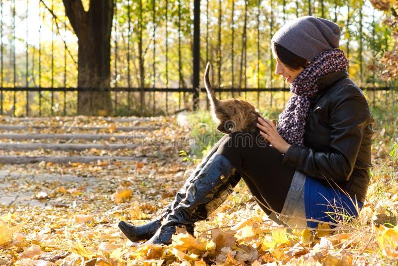 Chica joven con un gato al aire libre imágenes de archivo libres de regalías
