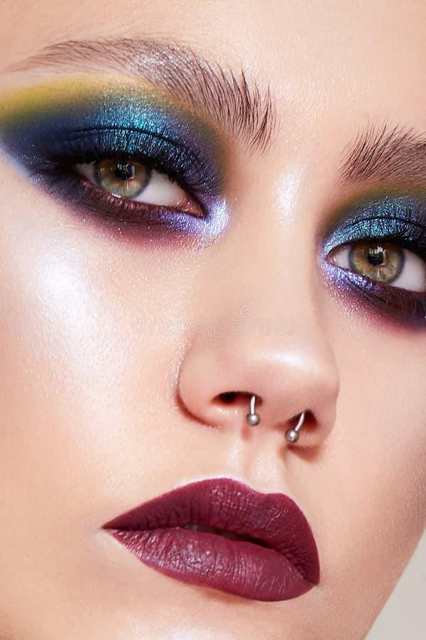 Chica joven con un maquillaje creativo brillante y trenzas en su cabeza Modelo hermoso con la piel brillante en la imagen del ing imagenes de archivo