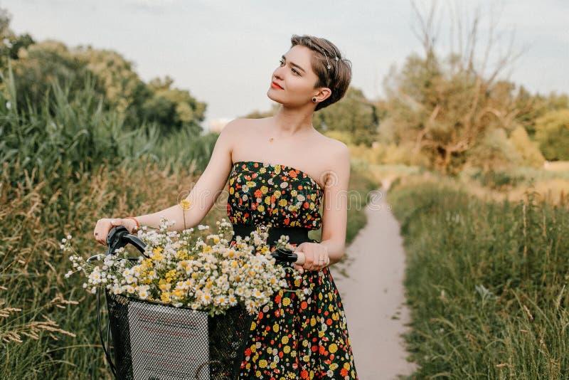 Chica joven con una bici Mujer y flores hermosas en la cesta El caminar en la naturaleza Viajes imagen de archivo libre de regalías