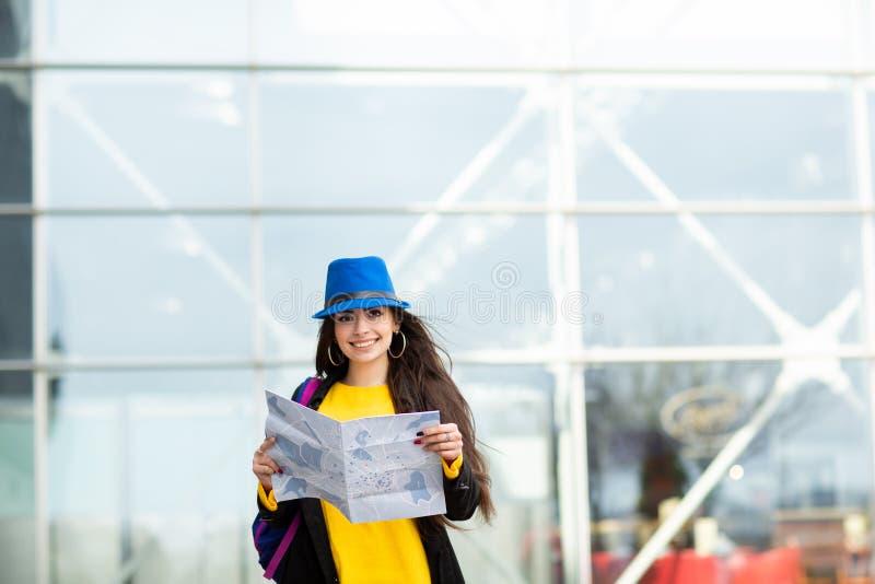 Chica joven con una mochila detr?s de su hombro que sostiene un mapa, en la calle cerca del aeropuerto fotografía de archivo libre de regalías