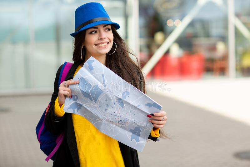 Chica joven con una mochila detr?s de su hombro que sostiene un mapa, en la calle cerca del aeropuerto imagen de archivo