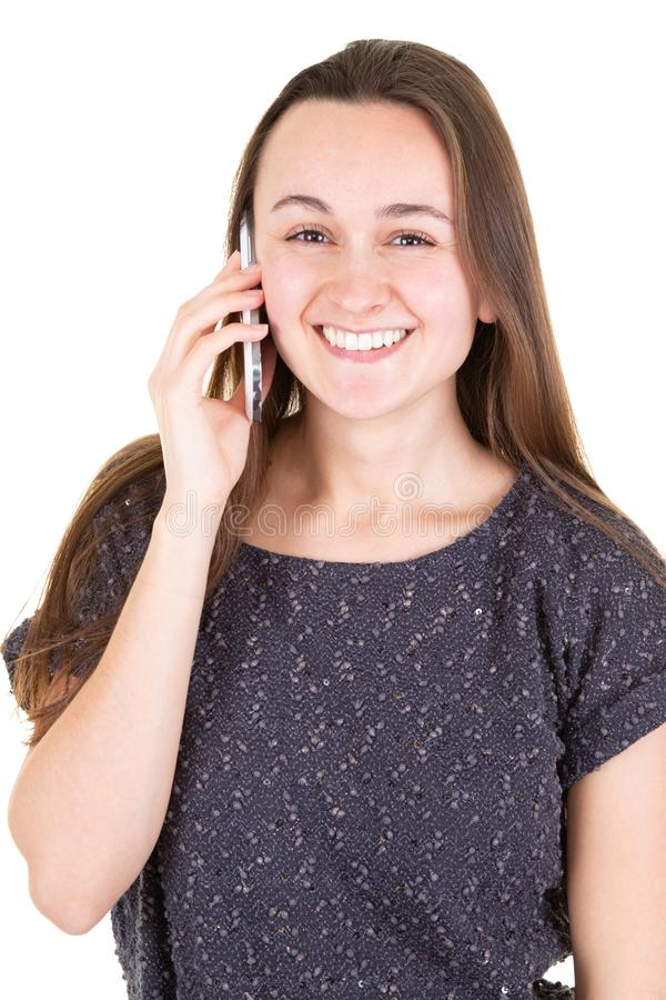 Chica joven confiada en camisa gris que habla en el teléfono y que mira la situación de la cámara delante del fondo blanco imagen de archivo libre de regalías