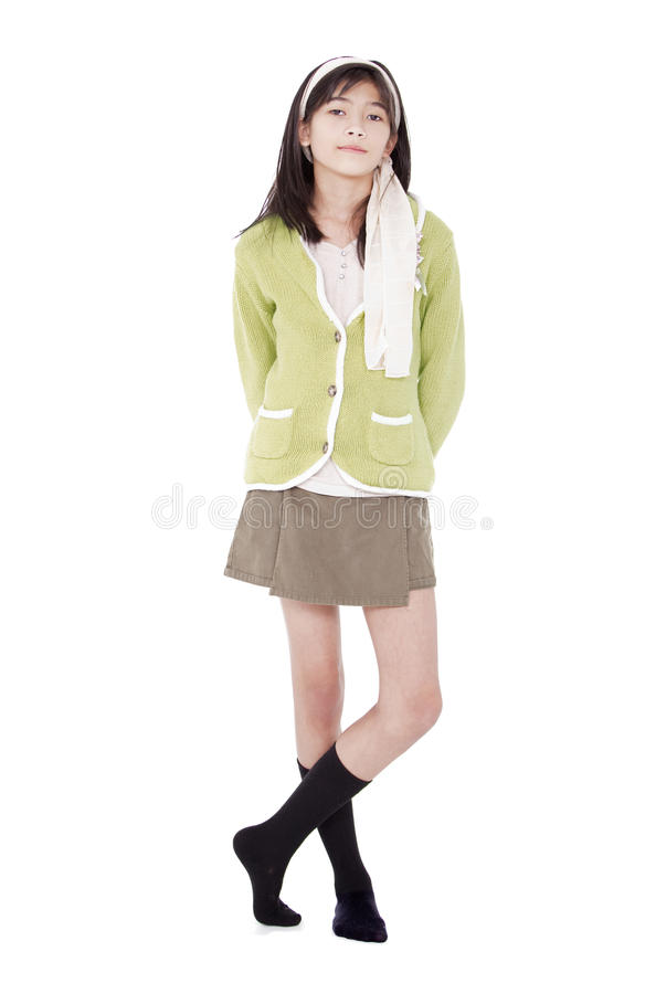 Chica joven confiada Unsmiling en la situación verde del suéter, isolat imagen de archivo