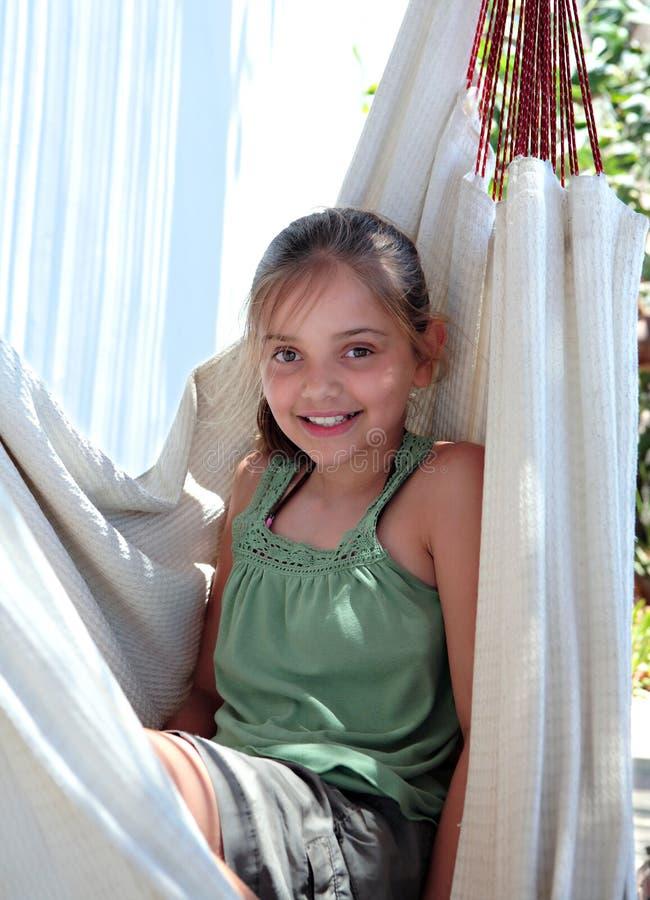 Chica joven confidente que se sienta en hamaca el vacaciones imagen de archivo