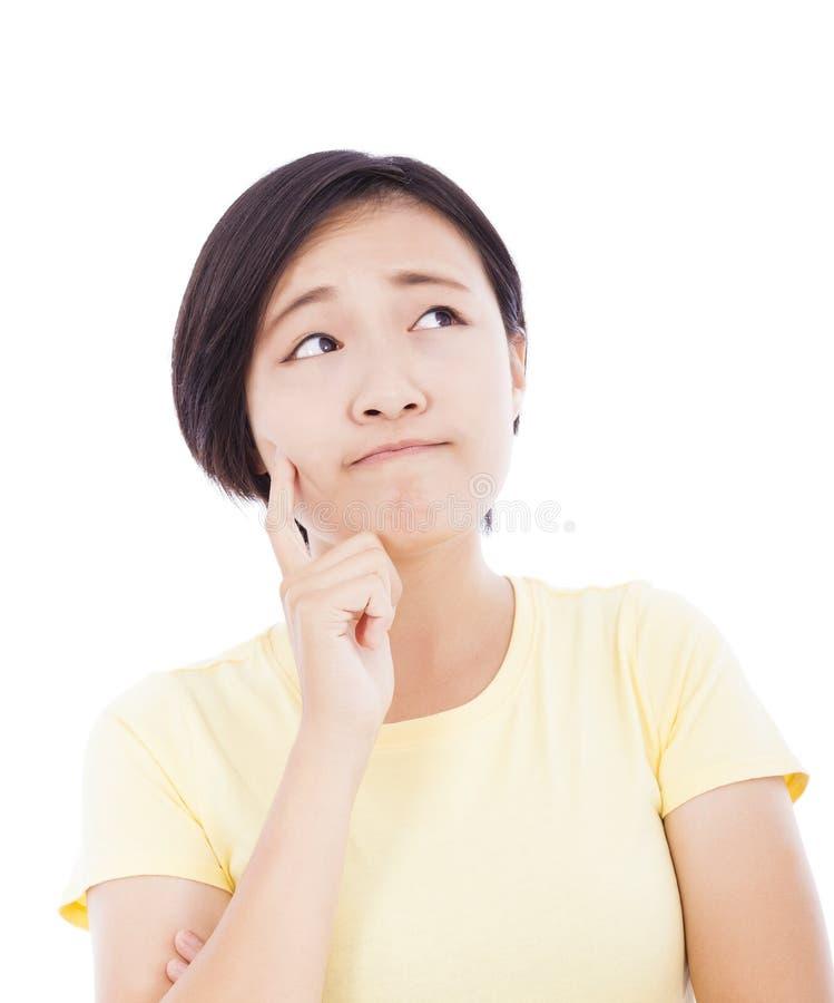 Chica joven confusa que piensa y que mira para arriba foto de archivo