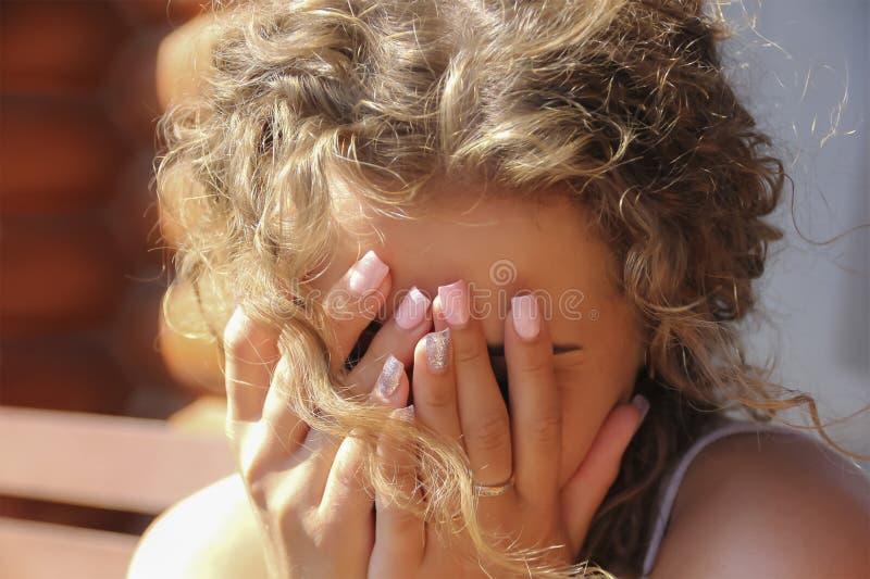 Chica joven, cubierta su cara con sus manos imagenes de archivo