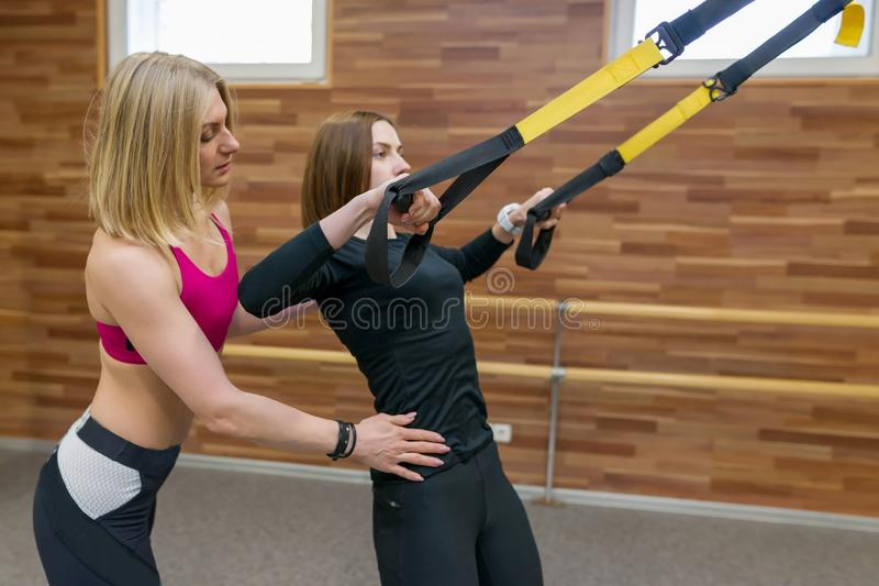 Chica joven de ayuda del instructor personal de sexo femenino de la aptitud para hacer ejercicios en gimnasio en correas de los l foto de archivo libre de regalías