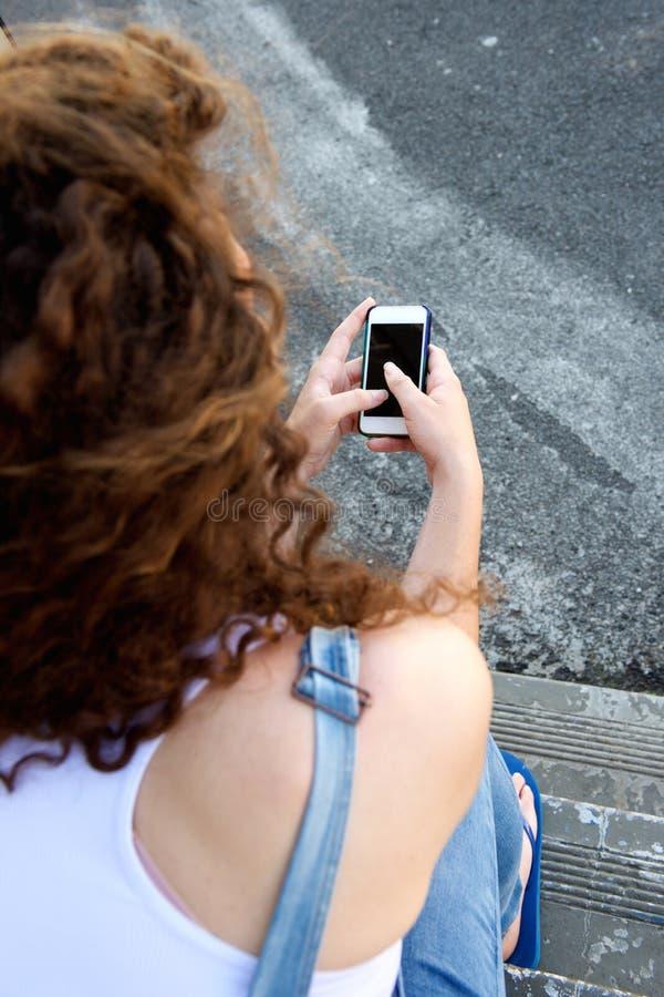 Chica joven de detrás el teléfono móvil que se sostiene y mandar un SMS foto de archivo libre de regalías