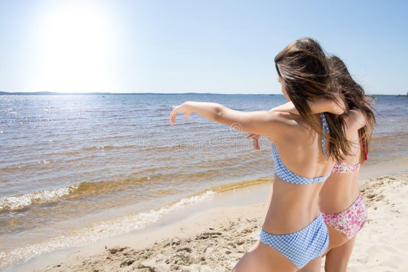 Chica joven de dos novias de los amigos que señala el mar imagen de archivo libre de regalías