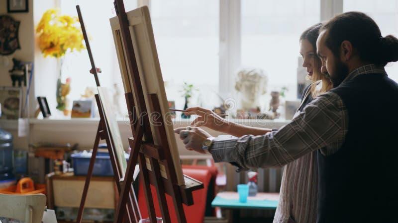 Chica joven de enseñanza del hombre experto del artista a las pinturas de dibujo y a explicar los fundamentos en estudio del arte imagenes de archivo