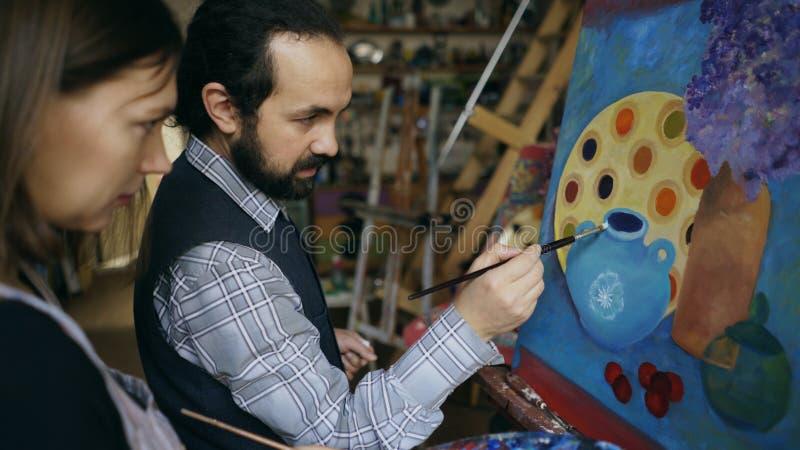 Chica joven de enseñanza del hombre experto del artista para dibujar pinturas y la explicación de los fundamentos de la luz en es imagen de archivo libre de regalías
