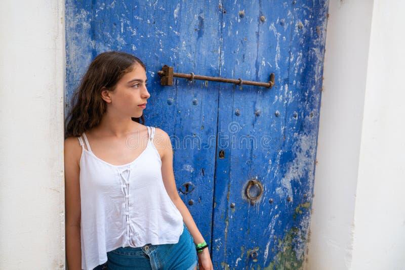 Chica joven de Ibiza Eivissa en puerta azul foto de archivo