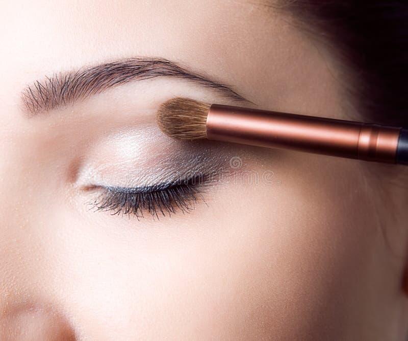 Chica joven de la belleza con los cepillos del maquillaje Natural compense a la mujer morena con los ojos del bleu Cara hermosa m foto de archivo libre de regalías