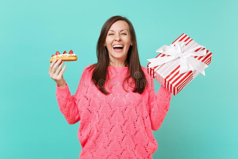 Chica joven de risa en caja rayada roja hecha punto del suéter del control de la torta rosada del eclair actual con la cinta del  fotos de archivo