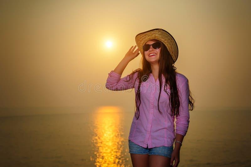Chica joven de risa en el sombrero y las gafas de sol del verano que pasan por alto puesta del sol hermosa Resto en el mar, viaje imágenes de archivo libres de regalías